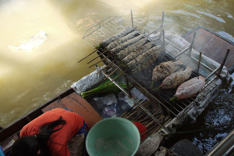 High angle view of woman by food on barbecue in boat at lake