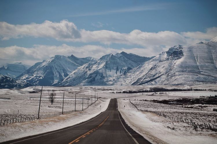 Empty road by snowcapped mountains against sky