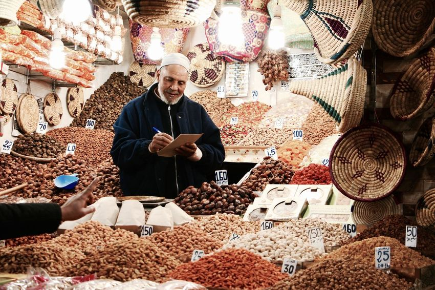Preparation  Workshop Confidence  Front View People Industry Morocco Marrakesh Jemaa El Fnaa Vendor Nuts Almonds Dates Palm Tree Vending Machine Patience Customer  Buying Food Harvest Market Market Stall Food Market Interaction Night Lights The Street Photographer - 2017 EyeEm Awards