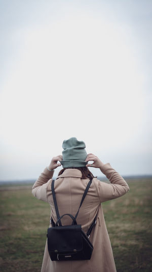 Rear view of woman photographing on field against sky