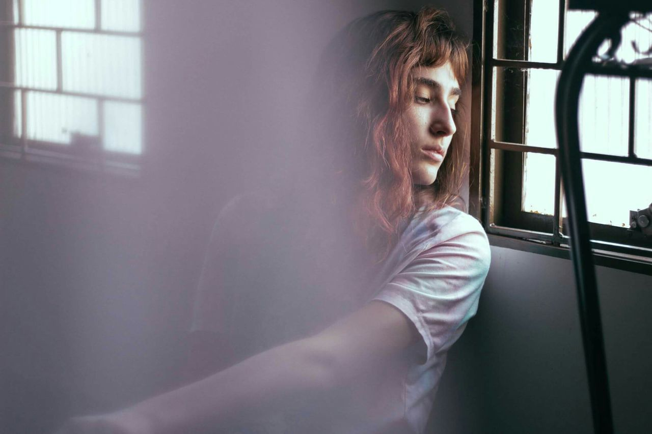 Depressed young woman sitting by window at home