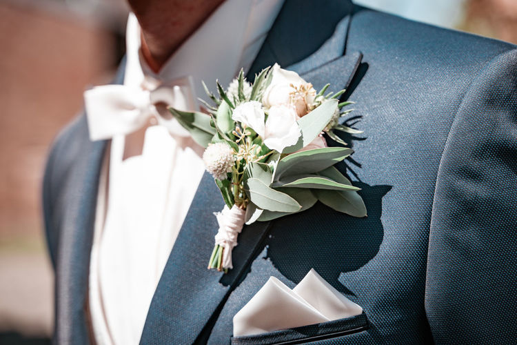 Midsection of bridegroom wearing boutonniere