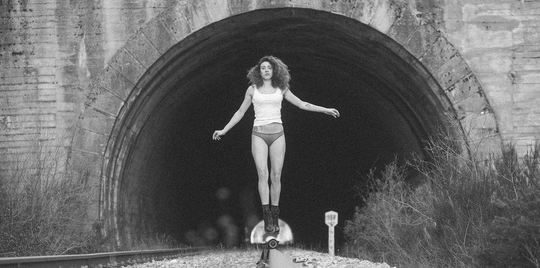 Portrait of woman levitating over railroad track