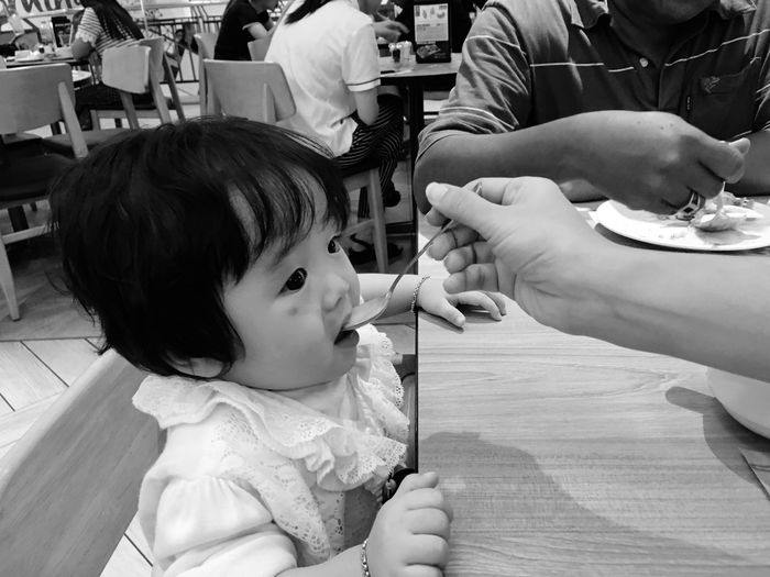 Cropped hand of mother feeding daughter in restaurant
