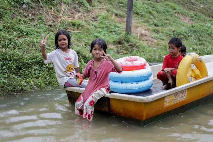 Kelantan. Malaysia : November 30, 2017. flood victims at kelantan Flood Victim Casual Clothing Cheerful Childhood Daughter Day Full Length Girls Happiness Lake Leisure Activity Lifestyles Nature Outdoors People Real People Sitting Smiling Togetherness Tree Vacations Water Waterfront Young Adult Young Women