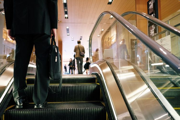 Adult Architecture City Consumerism Escalator Group Of People Illuminated Incidental People Indoors  Low Section Men Modern Motion Moving Walkway  People Railing Real People Staircase Transportation Travel Walking Women