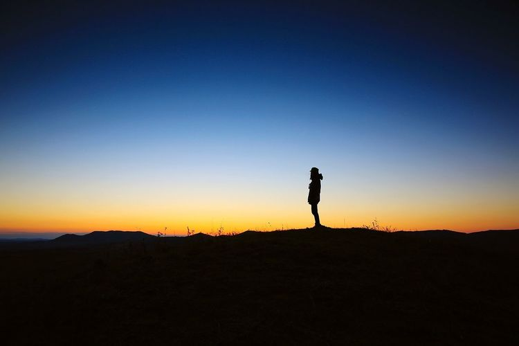 Silhouette woman walking on landscape against clear sky