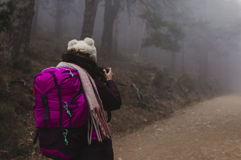 Rear view of female hiker on footpath amidst trees in forest