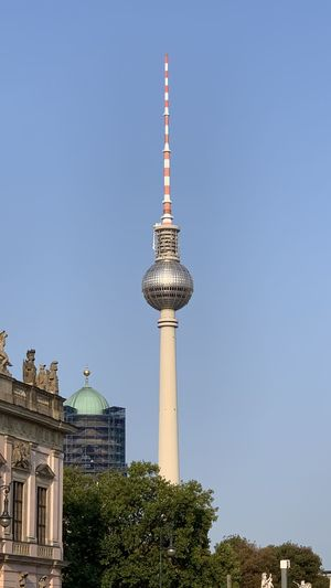 Low angle view of communications tower in city against clear blue sky
