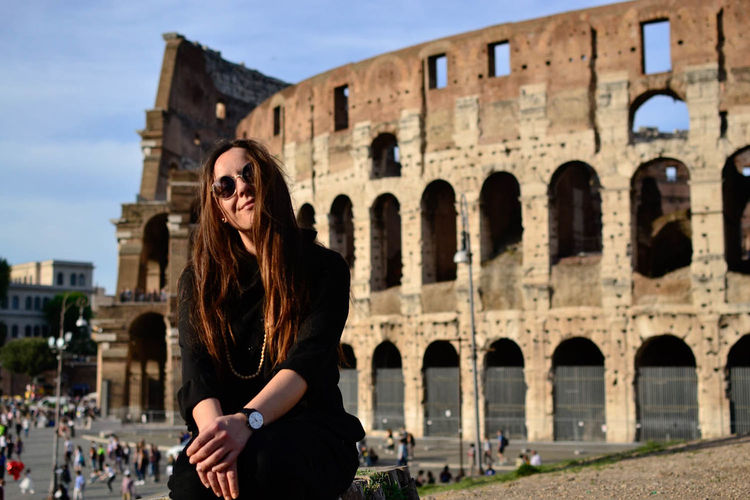 Mid adult woman sitting with coliseum in background