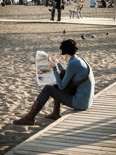 Real people of Barcelona Barcelona Beach Casual Clothing Leisure Activity Lifestyles Paper Read Reading Real People Side View Sitting SPAIN Blue Wave
