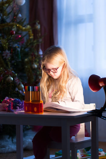 Girl Studying At Table During Christmas