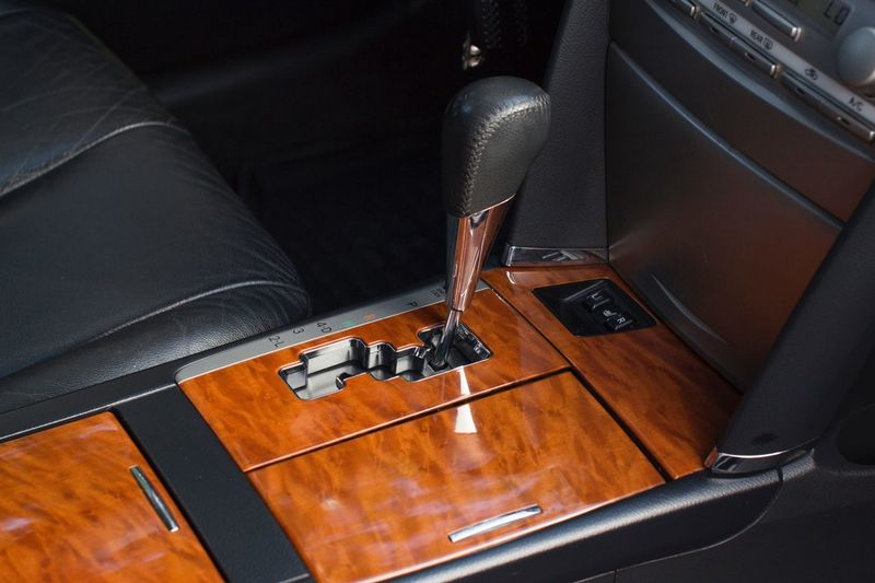 Shifting gear in leather and wooden car interior Road Trip Trip Leather Transport Driving Stick Car Gearshift Gear Technology Car Land Vehicle Motor Vehicle Mode Of Transportation Vehicle Interior Transportation Lifestyles