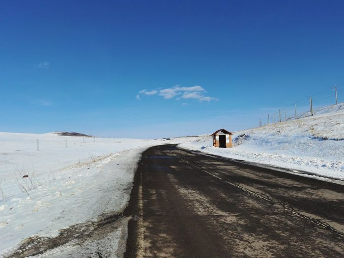 Road amidst snow covered land against blue sky