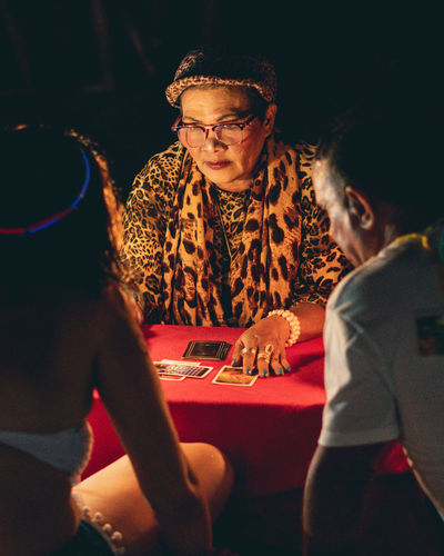 Tarot Reading Tarot Future Vision Future Vision Cheetah Print Cards Elderly Old Red Color Orange Color Illuminated Three People Reader Reading Table Couple - Relationship Couple Playing Cards Horoscope  Finger Ring Magical Moments Magical Glasses Playing