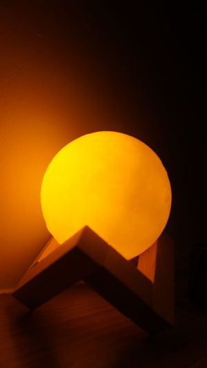 Low angle view of illuminated lamp against orange sky