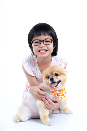 Isolated portrait Asian little girl holding Pomeranian dog with care on white background. Studio shot of girl and puppy Domestic One Person Domestic Animals Pets Mammal Animal Animal Themes Front View Canine Real People Dog Portrait Eyeglasses  Vertebrate Indoors  Small Pet Owner Casual Clothing White Background Pomeranian Puppy Happy Isolated Cheerful Friendship Love
