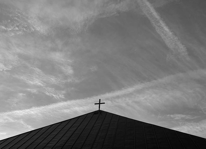 Low angle view of cross on roof of building against sky