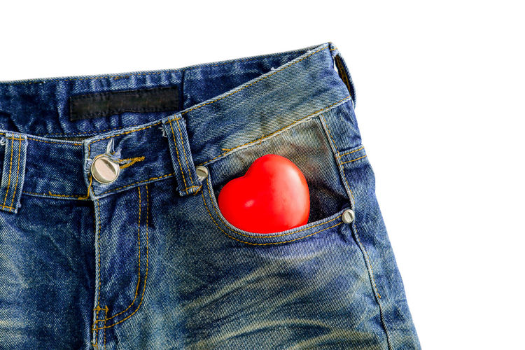 Close-up of red heart shape in jeans pocket against white background