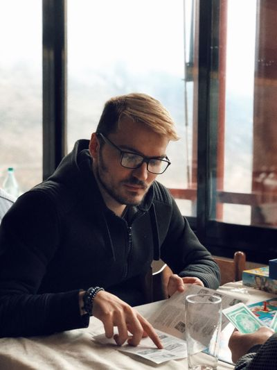 Eyeglasses  Sitting Indoors  One Person Real People Glasses Table Young Adult Young Men Concentration Window Casual Clothing Beard