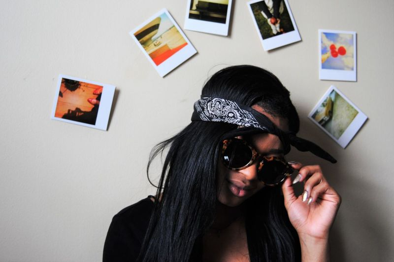 Close-up of woman wearing sunglasses against photographs stuck on wall