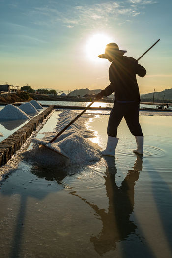 The daily activities in a salt village in Vietnam. Real People Sky Standing Leisure Activity Nature Lifestyles Outdoors Water One Person Sunset Full Length Reflection Men Sunlight Activity Fishing Beauty In Nature Beach Rear View Sun Sunrise Reflection Hat Salt