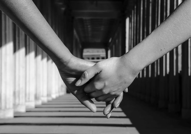 Cropped image of friends holding hands at corridor