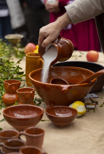 "A man is preparing queimada (traditional Galician hot drink made with flamed ""orujo"", sugar and lemon) Food And Drink Human Hand One Person Real People Bowl Holding Pouring Table Preparation  Asturias SPAIN Village Autumn Cloudy Travel Outdoors Vertical Preparing Orujo  Queimada Crockery Tradition Holiday"