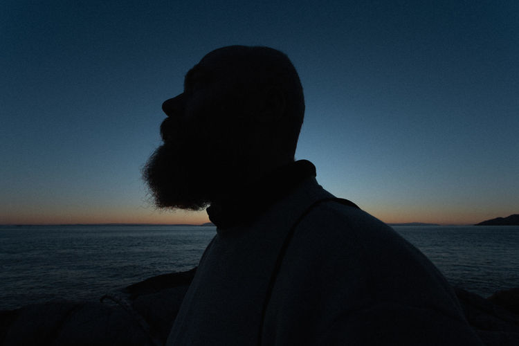 Silhouette man at beach against clear sky during sunset