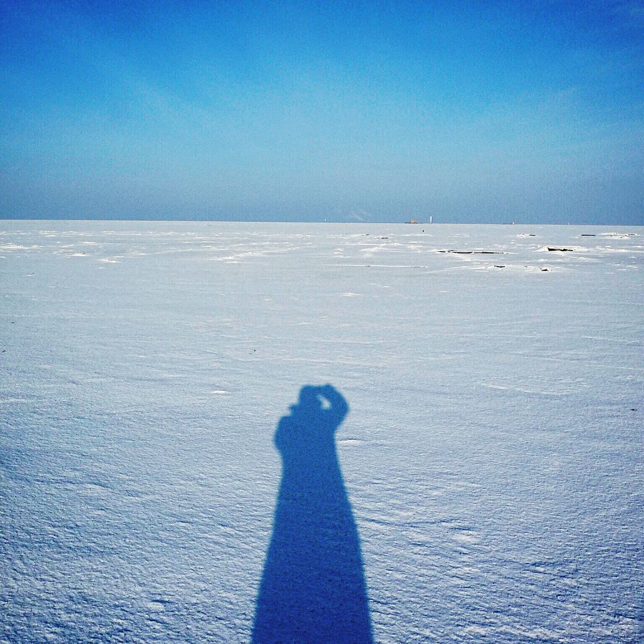 Shadow of man on snow covered field against clear blue sky