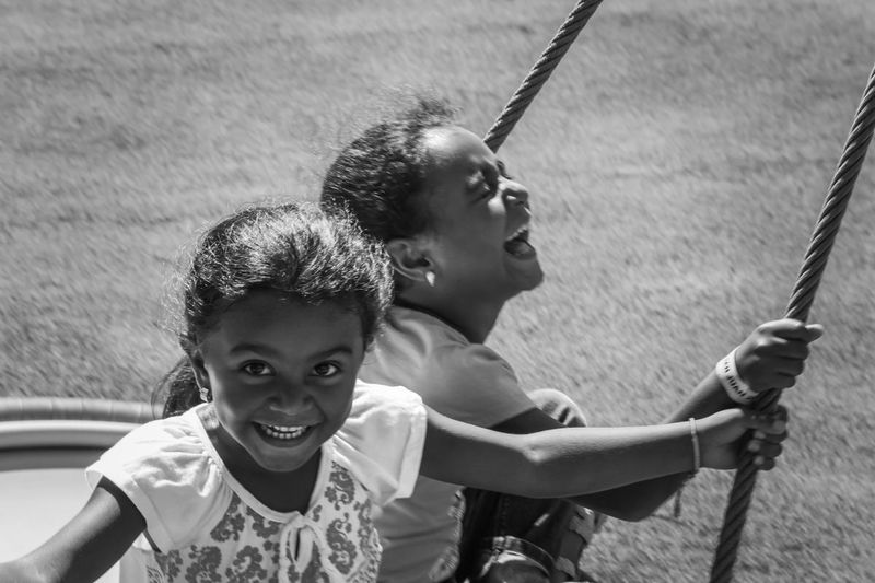 Portrait Of Smiling Girls On Swing At Playground