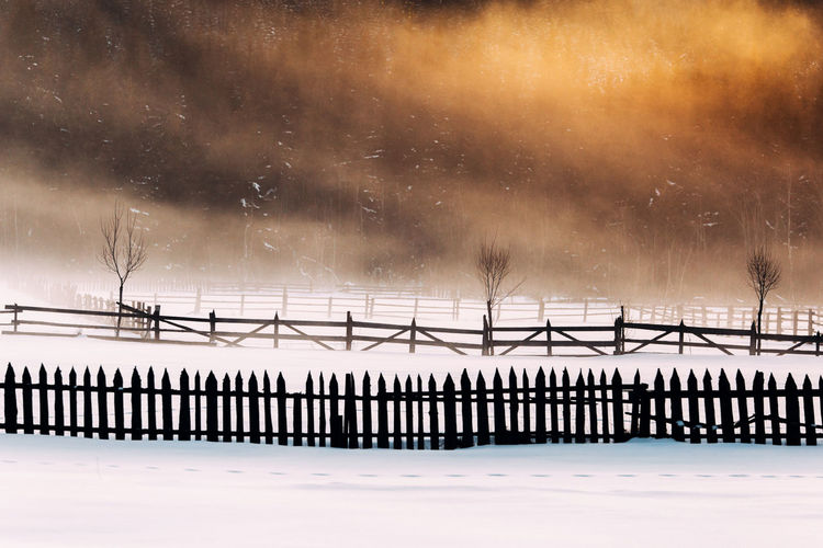 Fences on snow covered field during sunset