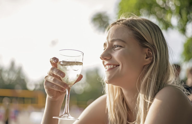 Smiling young woman having wine