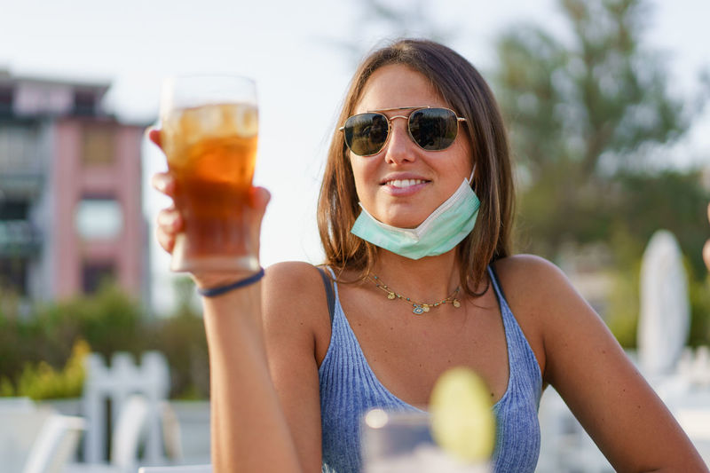 Portrait of a smiling young woman drinking glass with coronavirus face mask