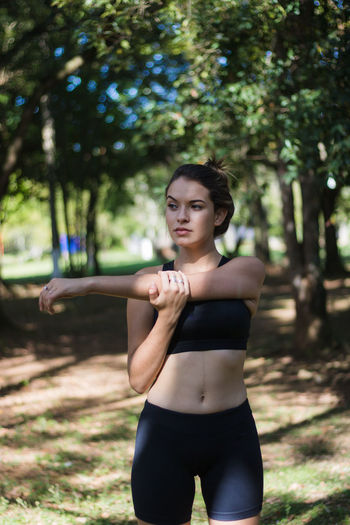 Teenage girl stretching hands looking away while exercising in park