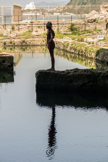 Full length of woman standing on retaining wall by lake
