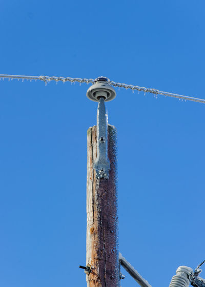 Low angle view of frosted power line against clear blue sky