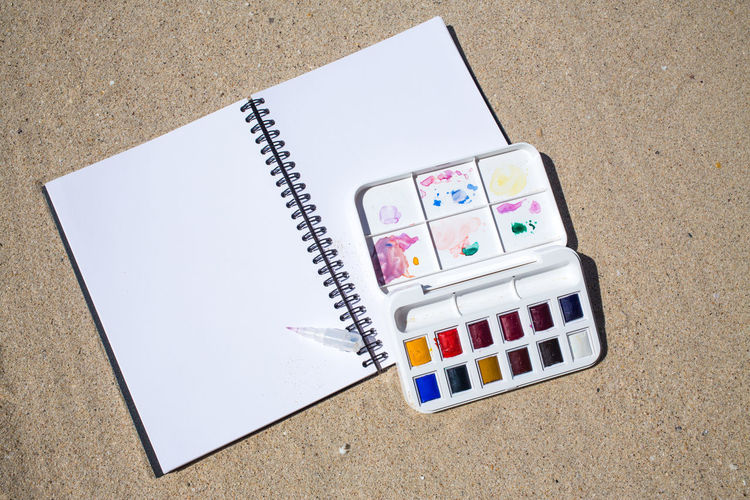 Notebook & Watercolor box on beach background Artist Box Colors Creativity Objects PaintBox Rainbow Colors Textured  Backgrounds Beach Brush Close-up Colorful Decoration Drawing Hobby Multicolors  Notebook Paintbrush Painting Plastic Sand Thailandtravel Watercolor Watercolor Painting