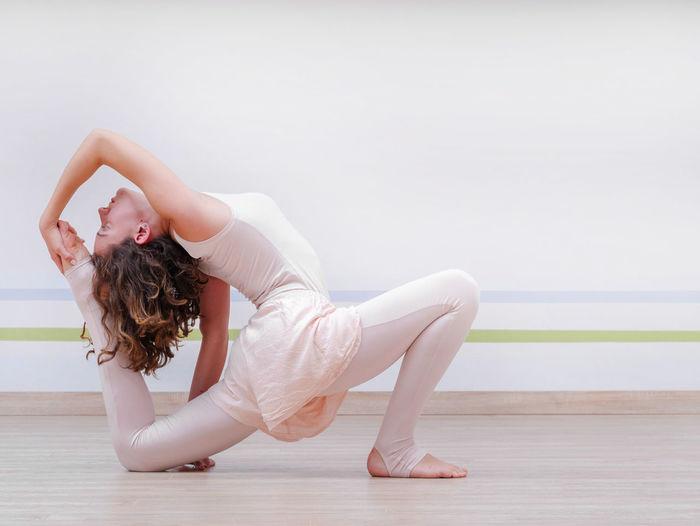 Young woman exercising in yoga studio