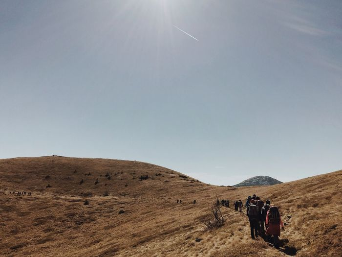 Rear View Of Hikers Walking On Mountain Against Sky During Sunny Day