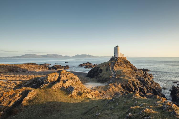 Llanddwyn Lighthouse On Mountain Against Sea