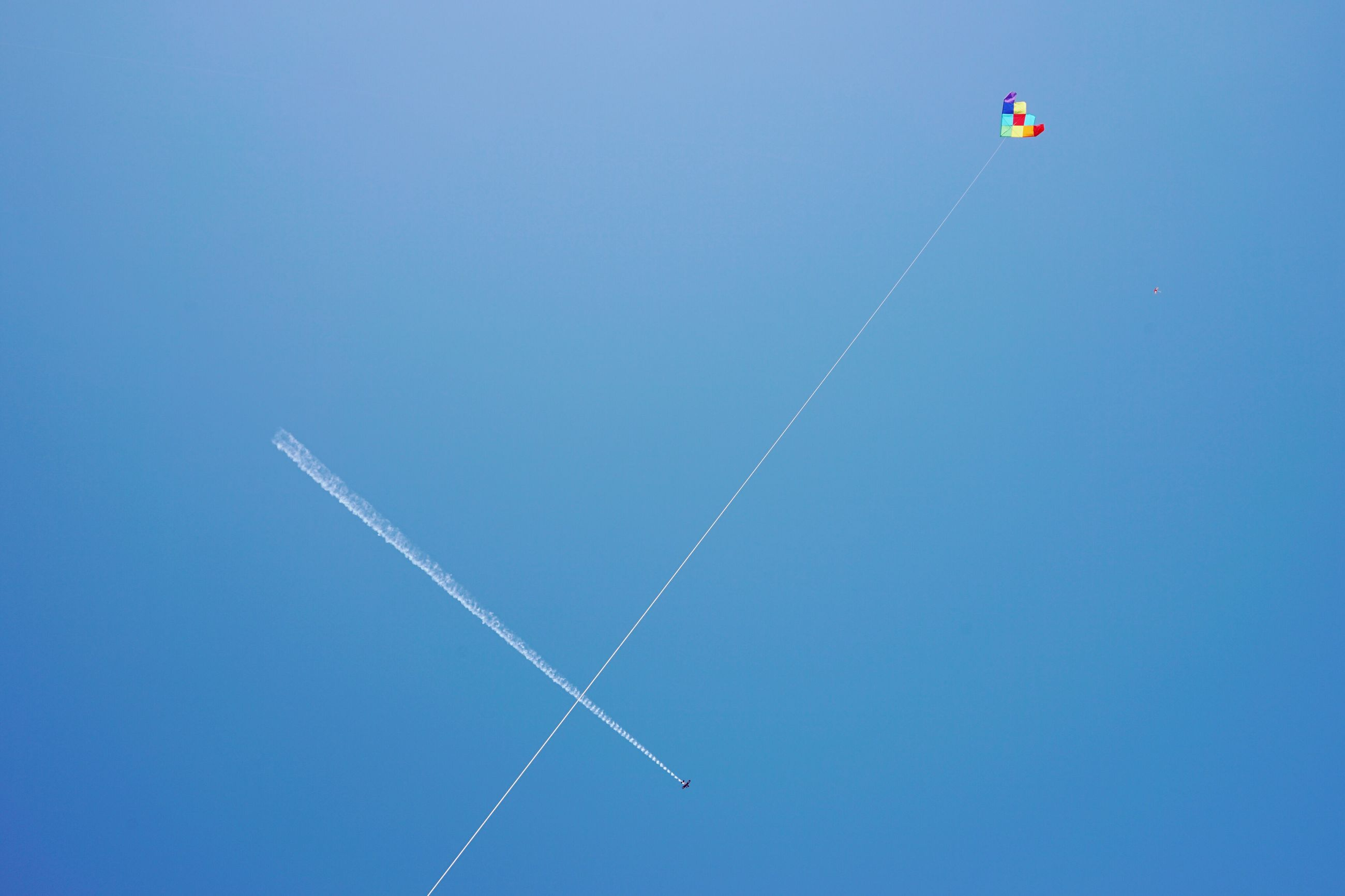 clear sky, copy space, blue, flying, low angle view, transportation, flag, vapor trail, mid-air, airplane, air vehicle, day, outdoors, no people, mode of transport, travel, nature, tranquility, wind, identity