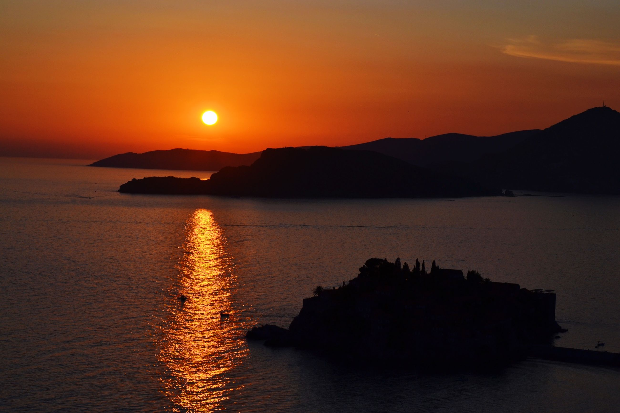 sunset, water, sea, scenics, sun, orange color, tranquil scene, mountain, beauty in nature, tranquility, reflection, silhouette, idyllic, waterfront, sky, nature, mountain range, sunlight, clear sky, rippled