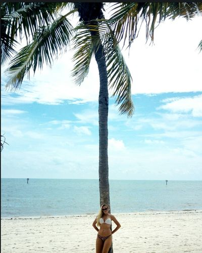 Beautiful Woman Standing By Coconut Palm Tree At Beach Against Sky