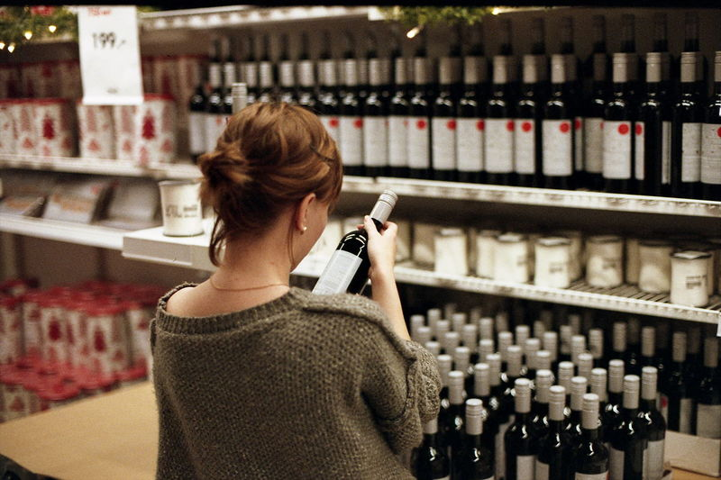 Rear view of woman holding wine bottle at store