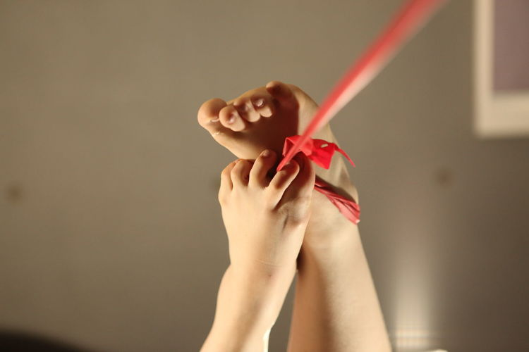 Close-up of legs holding red ribbon at home