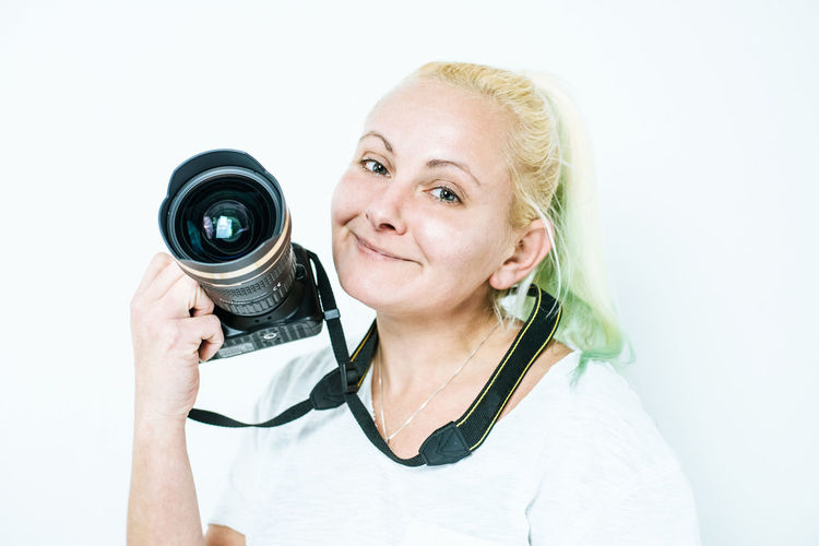 Close-Up Portrait Of Smiling Woman Holding Camera Against White Background