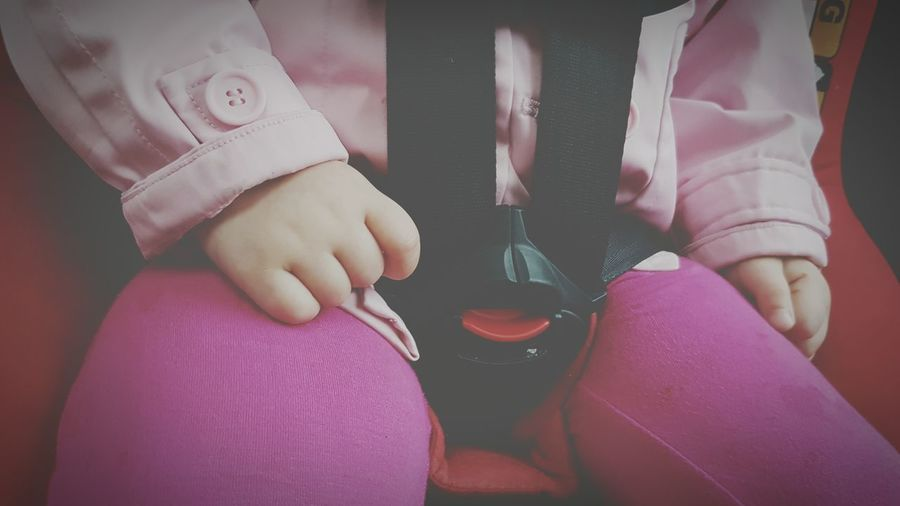 Midsection of child sitting on car seat