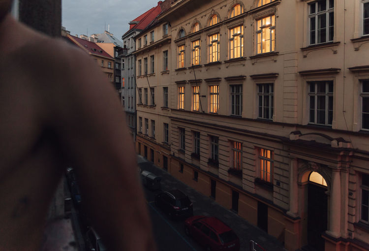 Midsection of man standing by building at dusk