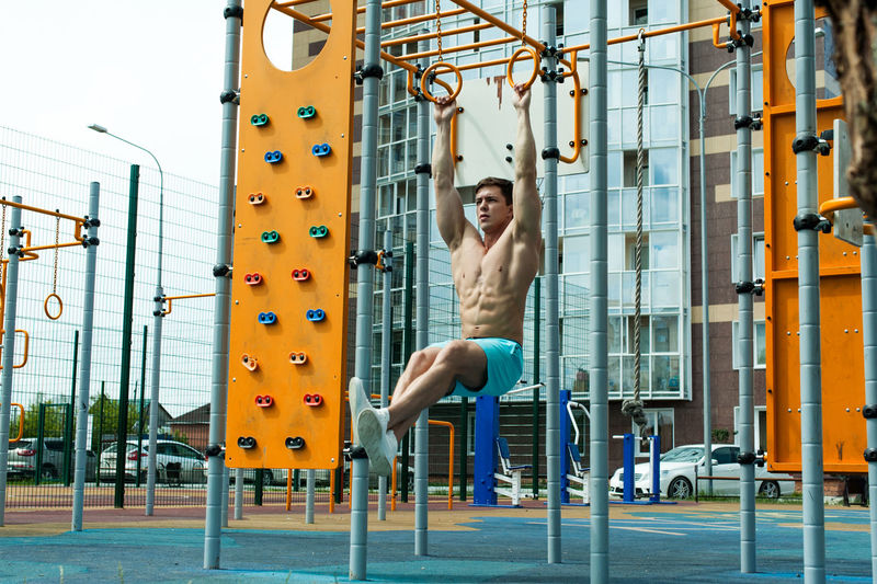 Shirtless young man exercising on gymnastic rings against building